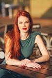 绿色礼服的美丽的年轻红发妇女 免版税图库摄影
