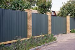 绿色篱芭和门在街道在花床附近在路附近 免版税库存图片