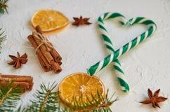 绿色糖果锥体的心脏和被弄脏的圣诞树分支用圣诞节香料-肉桂条,茴香星,烘干了桔子 库存照片