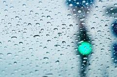 绿色红灯通过在雨下落的汽车玻璃 特写镜头,选择聚焦 免版税库存照片