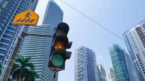 绿色红绿灯在有黄色发怒步行路牌的城市和都市都市风景在背景中 免版税库存图片
