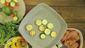 绿色绿皮胡瓜在一个格栅平底锅的黄油油煎对鸡的装饰品的 股票录像