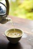 绿色罐倾吐的茶 免版税库存图片