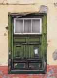 绿色老破旧的窗口在有被风化的木头的一个腐朽的房子里 免版税库存图片