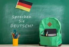 """绿色背包,有文本的""""黑板;Sprechen西埃德意志?"""";德国的旗子,学校用品和笔记本 免版税库存图片"""