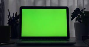 绿色膝上型计算机屏幕 黑暗的办公室 左到右移动式摄影车的移动 完善投入您自己的图象或录影 技术绿色屏幕  股票录像