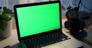 绿色膝上型计算机屏幕 黑暗的办公室 左到右移动式摄影车的移动 完善投入您自己的图象或录影 技术绿色屏幕  影视素材