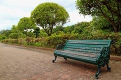 绿色色在路的木和锻铁长凳在公园里 免版税图库摄影