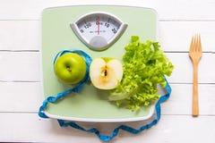 绿色苹果、新鲜蔬菜与重量标度和测量的磁带健康饮食减肥的 免版税库存照片