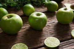 绿色苹果和切的柠檬在木桌上安排了 库存图片