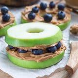 绿色苹果环绕用花生酱和蓝莓在木桌,方形的格式上 库存照片