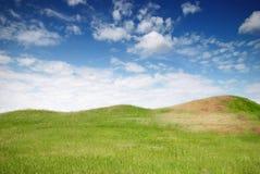 绿色草甸、小山和蓝天 库存图片