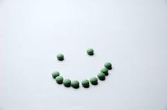 绿色药片微笑 库存照片