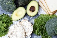 绿色菜和面包在灰色背景,顶视图,健康食品概念 免版税库存照片