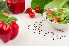 绿色菠菜,西红柿切片,在白色碗的红色辣椒粉春天新鲜的沙拉在白色木背景,特写镜头,拷贝空间 免版税库存图片