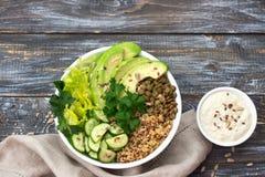 绿色菩萨碗用扁豆、奎奴亚藜、鲕梨、黄瓜、新鲜的莴苣、草本和种子 免版税库存照片