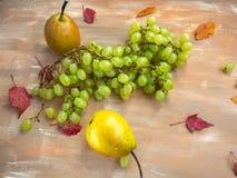 绿色葡萄和梨在木背景,秋叶刷子  库存照片