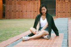 绿色衬衣妇女坐草坪 免版税图库摄影