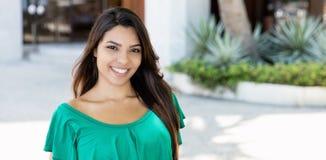 绿色衬衣的笑的拉丁美洲的妇女 免版税库存图片