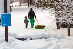 绿色裤子的人有他们的儿子的度过周末在森林向在小山的驱动求助并且进站在他们后的雪撬 库存照片