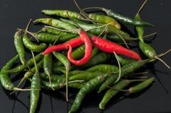 绿色辣椒和红色在黑背景 免版税库存图片