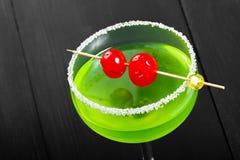 绿色酒精鸡尾酒用在一块玻璃的樱桃在黑暗的背景 免版税库存照片