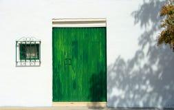 绿色门和窗口在白色墙壁上在Pedrera,安大路西亚 图库摄影