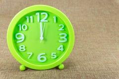 绿色闹钟在棕色麻袋布背景展示12:00 a M 免版税库存图片