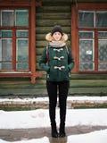 绿色附头巾皮外衣帽子的可爱的愉快的年轻红头发人妇女获得乐趣在多雪的冬天街道反对绿色木小屋 免版税库存照片