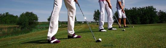 绿色领域的三名高尔夫球运动员 免版税库存照片