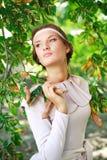 绿色黄色叶子的可爱的女孩 免版税库存照片