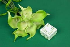 绿色黄色水芋百合花束与礼物盒和白色心脏的在绿色纸板背景 库存图片