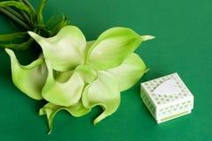 绿色黄色水芋百合花束与礼物盒和白色心脏的在绿色纸板背景 免版税图库摄影