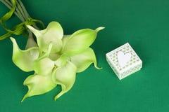 绿色黄色水芋百合花束与礼物盒和白色心脏的在绿色纸板背景 库存照片