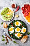 绿色shakshuka用菠菜、无头甘蓝和豌豆 健康可口早餐用鸡蛋,柑橘沙拉,鲕梨 顶视图,顶上 库存图片
