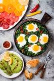 绿色shakshuka用菠菜、无头甘蓝和豌豆 健康可口早餐用鸡蛋,柑橘沙拉,鲕梨 顶视图,顶上 免版税库存照片