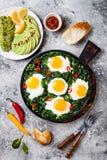 绿色shakshuka用菠菜、无头甘蓝和豌豆 健康可口早餐用鸡蛋,柑橘沙拉,鲕梨 顶视图,顶上 免版税库存图片