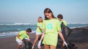 绿色T恤杉的四个志愿者有图象的回收收集在海滩的垃圾,看在与袋子的照相机收集 影视素材