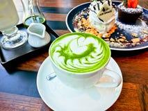 绿茶拿铁用在木桌,绿茶背景上的点心 图库摄影