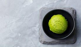 绿茶matcha在黑碗的冰淇凌瓢在灰色石背景 复制空间 顶视图 免版税库存照片