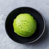 绿茶matcha在黑碗的冰淇凌瓢在灰色石背景 顶视图 关闭 库存图片