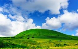 绿草小山和蓝天 免版税库存照片
