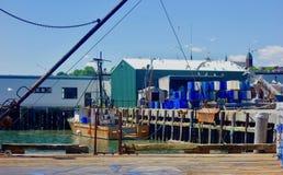 缅因龙虾码头码头,靠码头的小船,捕鱼业波特兰缅因2018年6月运作的江边 免版税库存照片