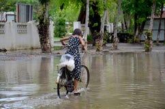 缅甸女孩骑马自行车在水灾地区 库存照片