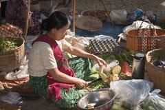 缅甸妇女切开了在亚洲开放的市场上的菜 库存图片