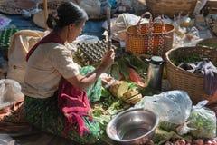 缅甸妇女切开了在亚洲开放的市场上的菜 库存照片