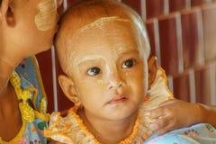 缅甸小孩画象有Thananka的在面孔,缅甸- 2017年11月21日 免版税库存照片