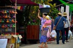 缅甸母亲举行婴孩和运载的水池塑料在她的h 免版税图库摄影
