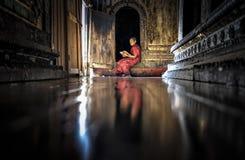缅甸- 2016年12月5日:在寺庙前面,单区的门的缅甸小的新手修士读书佛教书 免版税库存照片
