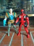 缆绳& Deadpool在壁炉前面的砖戏弄 免版税库存照片
